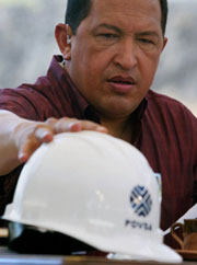 Hugo Chavez reaches for his safety hat