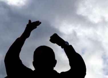 Chavecito silhoutted against the sky, doing his famous palm-punch